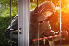 Burglar breaking in a house Stock Photos