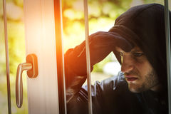 Burglar breaking in a house. Burglar wearing black clothes and leather coat breaking in a house Stock Photography