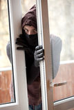 Burglar breaking into a house through window Stock Photos