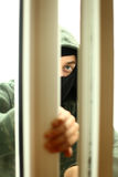 Burglar breaking into a house through window Royalty Free Stock Photography