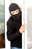 Burglar breaking into a house through window Royalty Free Stock Image