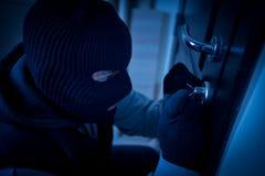 Burglar breaking the lock of a door royalty free stock photo