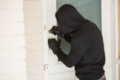 Burglar breaking open the door Stock Image