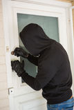 Burglar breaking open the door. Of someones home Royalty Free Stock Photography