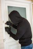 Burglar breaking open the door Royalty Free Stock Photography