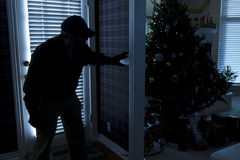 Burglar Breaking In To Home At Christmas Through B Stock Image