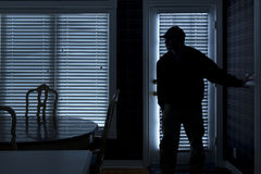 Burglar Breaking In To Home At Night Through Back
