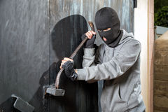 Burglar breaks lock on door Stock Image