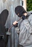 Burglar breaks lock on door Royalty Free Stock Image