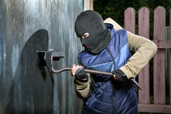 Burglar breaks lock on door Royalty Free Stock Photos