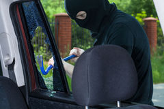 A burglar breaks a window with a crowbar. In the car stock images
