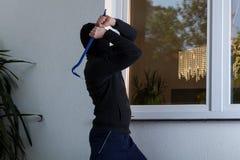 Burglar breaks the window stock photography