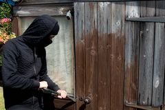 Burglar. Breaking into ready to enter a property stock image