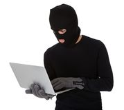 Burglar on computer. Thief in disguise stealing data from computer Stock Photo