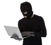 Burglar on computer Stock Photo