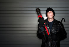 Burglar with Crowbar. Young burglar in leather jacket with crowbar stock images