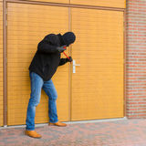 Burglar with a crowbar. Mean looking burglar enters a house stock photography