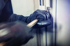 Burglar with crowbar break door to enter the house royalty free stock photo
