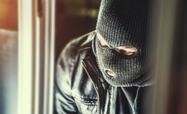 Burglar with crowbar break door to enter the house Stock Photo