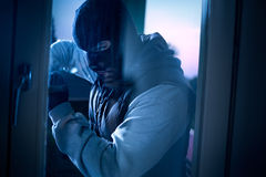 Burglar with crowbar breaking into a house Royalty Free Stock Photos