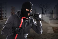 Burglar With A Crowbar And A Flashlight Stock Photos