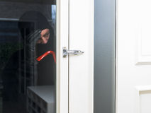Burglar with a crowbar. Mean looking burglar enters a house stock photo