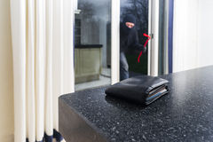Burglar with a crowbar. Mean looking burglar enters a kitchen to grab a wallet from the kitchen counter stock images