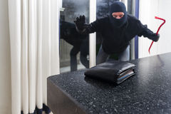 Burglar with a crowbar. Mean looking burglar enters a kitchen to grab a wallet from the kitchen counter royalty free stock image