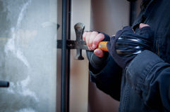 Burglar with crowbar to break door to enter the house.  stock images