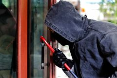 Burglar with crowbar trying break the door to enter the house stock photography