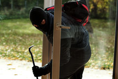 Burglar entering to house. Through the window Stock Images