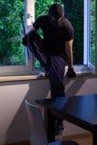 Burglar enters of someone's house. Burglar enters through the window of someone's house stock photography