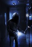 Burglar. With flashlight and crow bar in a dark office building Royalty Free Stock Photography