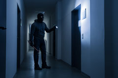 Burglar With Flashlight And Crowbar In Office Building Stock Images