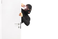 Burglar with flashlight entering through a door. Isolated on white background Stock Photography