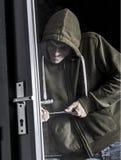 Burglar forcing door stock photography