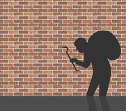 Burglar in front of brick wall Royalty Free Stock Image