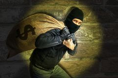 Burglar with full bag of money is catched with flash light at night. Burglar is carying full bag of money and is catched with flash light at night royalty free stock images