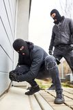 Burglar at gate of garage with crowbar. Two burglars at gate of garage with crowbar at burglary stock images