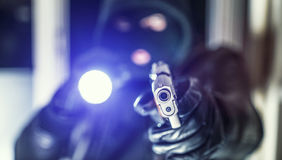Burglar with Gun and torch. Masked burglar with pistol gun breaking and entering into a victim`s home stock image