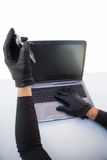 Burglar hacking laptop and mobile phone Stock Photo