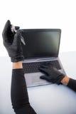 Burglar hacking laptop and mobile phone Stock Photo