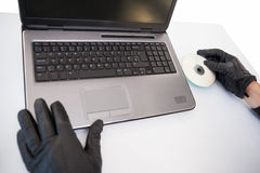 Burglar hacking and putting a cd-rom in laptop. On white background Stock Photography