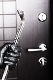Burglar hand holding crowbar break opening door. Crime scene - criminal thief or burglar hand in gloves holding metal crowbar break opening home door lock Stock Image