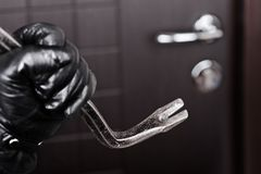 Burglar hand holding crowbar break opening door. Crime scene - criminal thief or burglar hand in gloves holding metal crowbar break opening home door