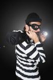 Burglar. With hat, mask, flashlight and money bag on black background stock image