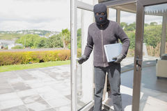 Burglar holding laptop. And leaving home stock photo