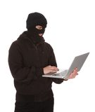 Burglar Holding Laptop. Burglar Wearing Mask Holding Laptop Over White Background stock image