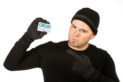 Burglar: Holding Stolen Credit Card. Series with Caucasian male as a burglar or thief, sneaking in a window, carrying stolen goods, etc. Isolated on white royalty free stock images