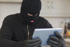 Burglar holding tablet pc Stock Photo